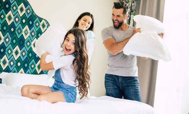 재미 있고 흥분된 가족은 큰 방의 침대에서 재미 있고 점프하고 함께 놀고 있습니다.