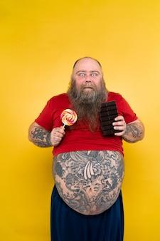 不健康な食べ物に飢えている面白くて陽気な太った男