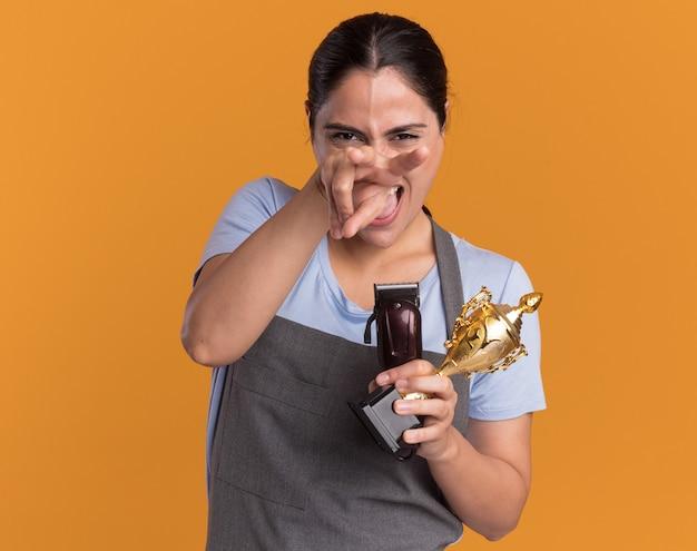 오렌지 벽 위에 서있는 앞에 손가락으로 가리키는 트리머와 금 트로피를 들고 앞치마에 재미 있고 즐거운 젊은 아름다운 여자 미용사