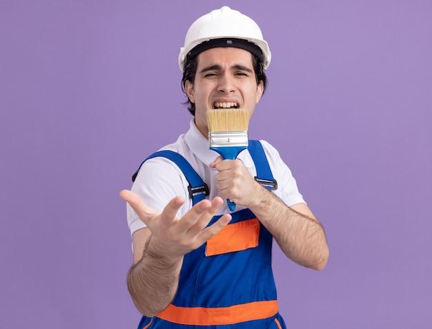 紫色の壁の上に立ってマイクの歌として使用してペイントブラシを保持している建設制服と安全ヘルメットの面白くて楽しい若いビルダー男