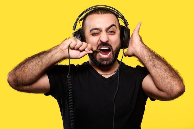 헤드폰에 수염을 가진 재미 있고 긍정적 인 남자는 음악을 듣고 노란색 와이어를 물었습니다. 국제 dj의 날