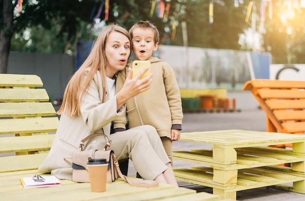 미취학 아동 아들과 함께 재미 있고 놀란 젊은 엄마가 벤치에 앉아