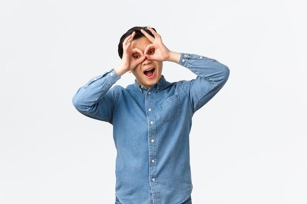 재미있고 낙관적이며 장난기 많은 아시아 남자가 얼굴을 하고, 손으로 눈을 가리고 가짜 안경을 보여주고, 누군가를 조롱하고, 놀고, 흥미진진한 것을 보고, 흰색 배경에 서 있습니다.