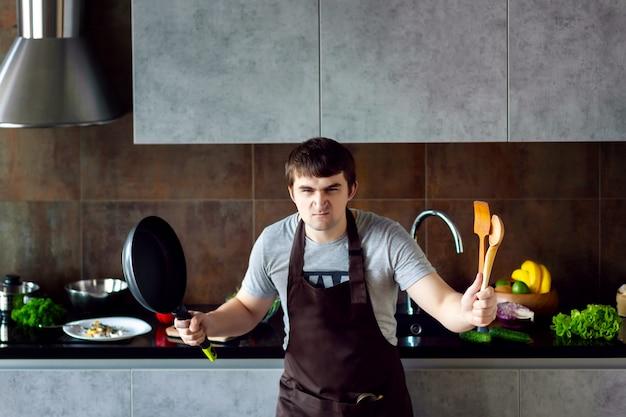 金属製のフライパン、木製の台所用品、エプロンを調理しようとすると面白い怒っている敗者の男性男性。失敗し、灰色のモダンなロフトキッチンで叫ぶ。キッチンのコンセプトに失敗した学士。