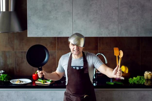 面白い怒っている敗者の男性男性の頭に金属鍋、フライパン、木製の調理器具を調理しようとすると、失敗し、灰色のモダンなロフトキッチンで叫ぶ。キッチンのコンセプトに失敗した学士。