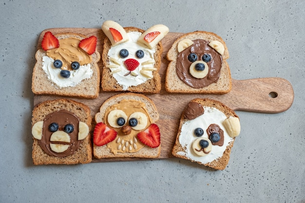 Funny animal faces toasts with butter, banana, strawberry, and blueberry