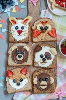 面白い動物は、スプレッド、バナナ、イチゴ、ブルーベリーのトーストに直面しています