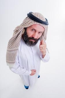재미있는 아랍 남자는 감정을 가지고 포즈를 취합니다. 광각 렌즈로 위에서 쐈어.