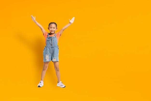 노란색 배경에 재미 아시아 아이 소녀 행복