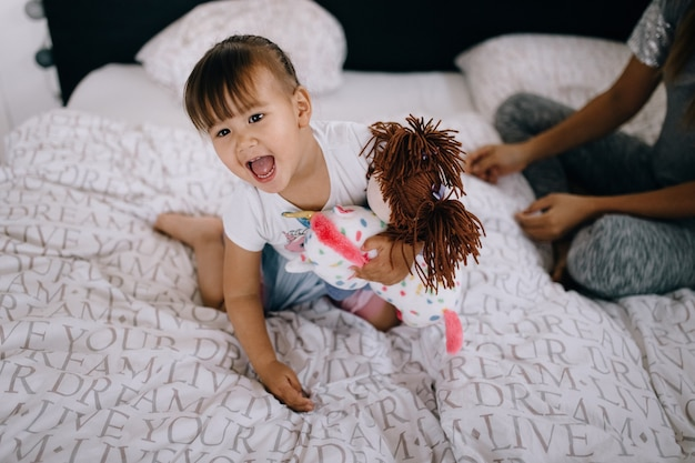 Funny asian girl playing with a doll at home