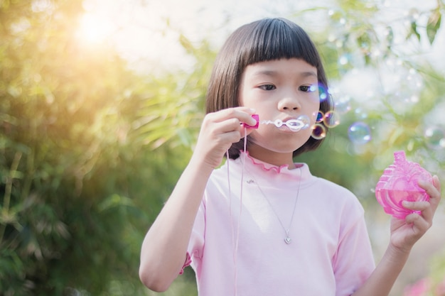 Funny asian kid blowing bubbles in park