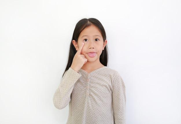 Забавная азиатская маленькая девочка, высунувшая язык, чтобы корчить рожи