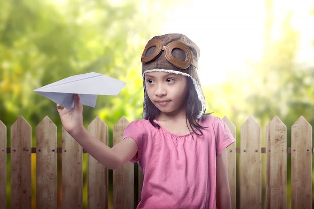 Funny asian little girl in aviator helmet playing toy airplane
