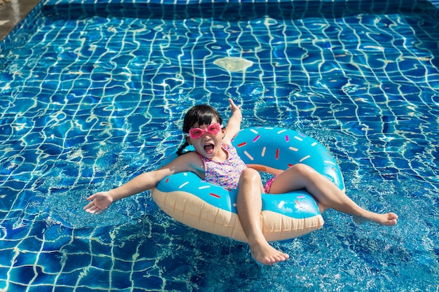 Funny asian little girl playing with colorful inflatable ring in outdoor swimming pool on hot summer day.