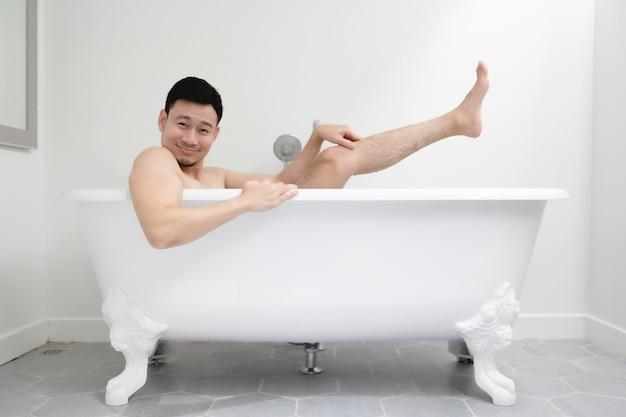 Забавный азиатский мужчина пытается быть сексуальным в белой ванной. концепция развлечения и отдыха.