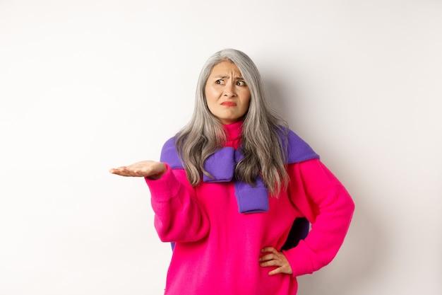 회색 머리를 한 재미있는 아시아 어머니는 불평하고 어깨를 으쓱하고 왼쪽 혼란스러운 표정을 하고 흰색 배경 위에 서 있는 이상한 것을 손으로 가리키고 있습니다.
