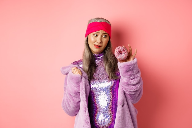 Funny asian senior woman in glittering disco dress and faux fur coat looking tempted at delicious donut, wanting to eat sweet, standing over pink background