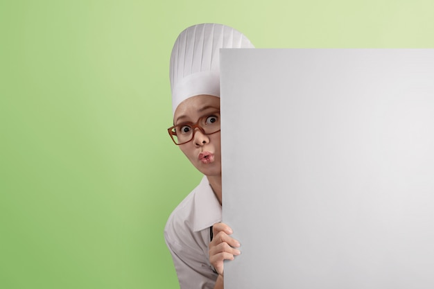 Funny asian woman chef peeking from behind blank copyspace