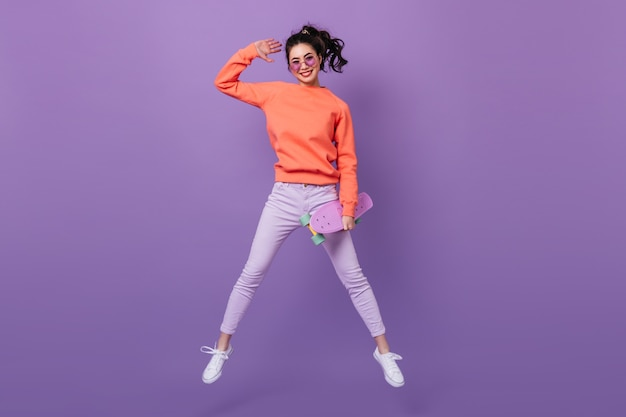 Смешная азиатская женщина в штанах прыгает на фиолетовом фоне. взгляд полной длины корейской молодой женщины с longboard.