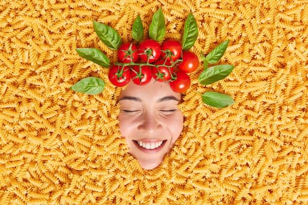 재미있는 아시아 여성은 생 파스타 미소를 통해 머리를 숙이고 토마토와 녹색 잎으로 둘러싸인 음식 재료로 화환처럼 유쾌하게 창의적인 사진을 만듭니다.
