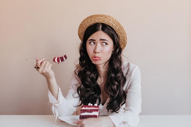 Donna asiatica divertente in cappello di paglia che mangia torta. bello modello femminile cinese che gode del dessert.