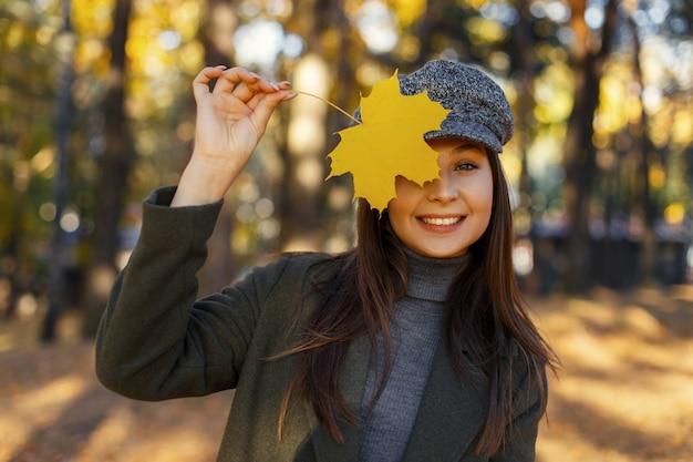 Смешная привлекательная красивая молодая счастливая женщина с улыбкой в винтажной шляпе и пальто закрывает лицо желтым осенним листом и наслаждается солнечным днем