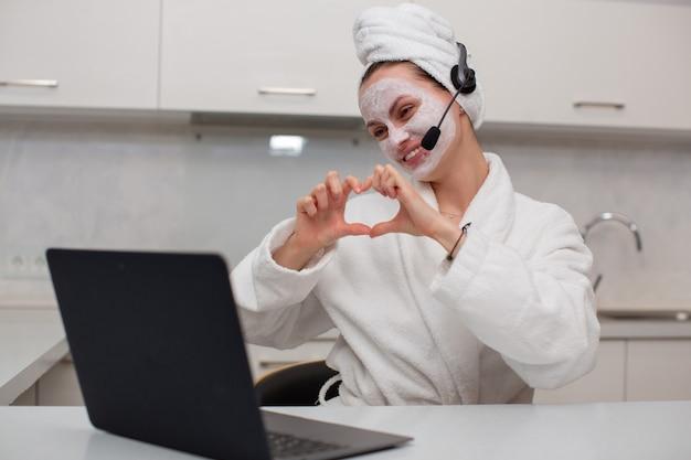 ウェブカメラのラップトップのヘッドセットで話している保湿フェイスマスクの面白い魅力的な女の子は彼女の手で心を高品質の写真にします