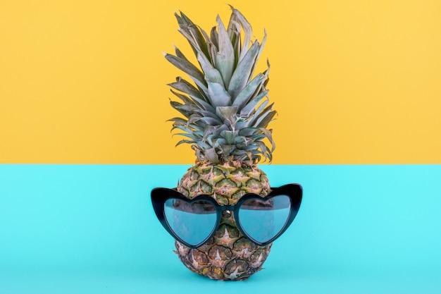 Забавный привлекательный ананас в стильных очках на желто-синем фоне. концепция летних каникул.