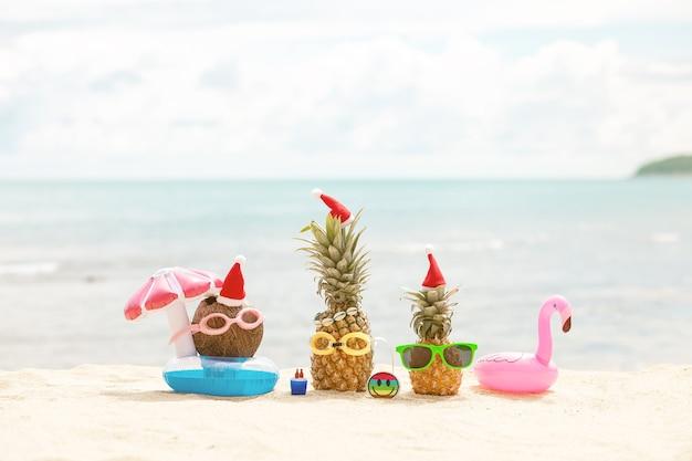 Забавные привлекательные ананасы и кокос в стильных солнцезащитных очках на песке на фоне бирюзового моря. в рождественских шапках.