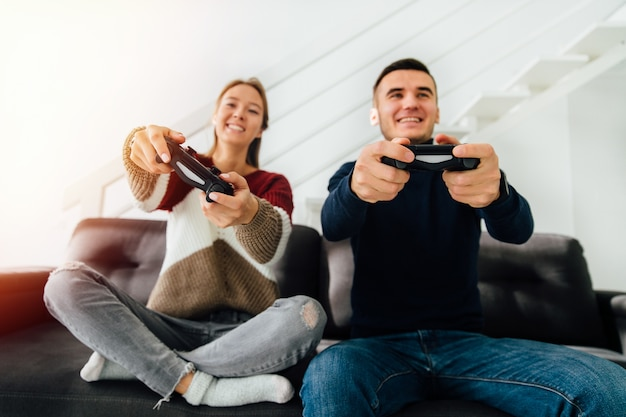 Funny attractive young couple playing computer games with joysticks, sitting on couch