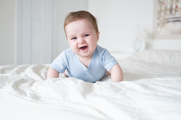 Funny baby boy 6 months old in blu bodysuit smiling and lying on bed at home.