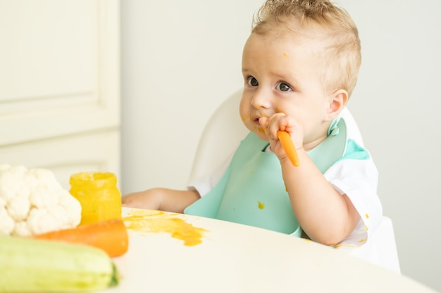 Funny baby boy in bib eating vegetable puree with spoon sitting in child chair. child learn to eat by himself.