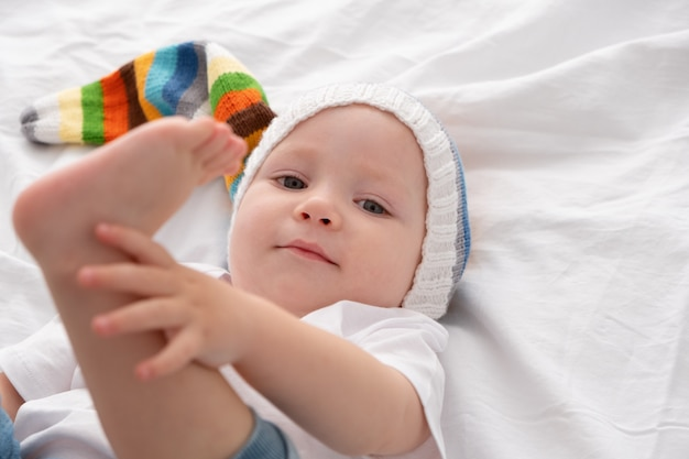 Funny baby boy in funny colorful hat smiling and lying on a white bedding at home.