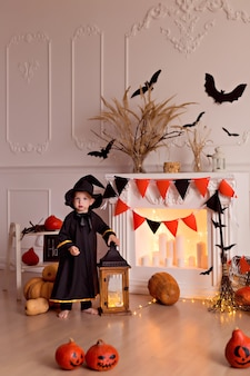 Funny baby boy in halloween witch costume with pumpkin jack and broom indoors