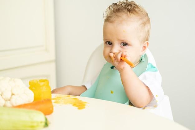 어린이 의자에 스푼으로 앉아 야채 퓌레를 먹는 턱받이에 재미있는 아기. 아이는 스스로 먹는 법을 배웁니다.