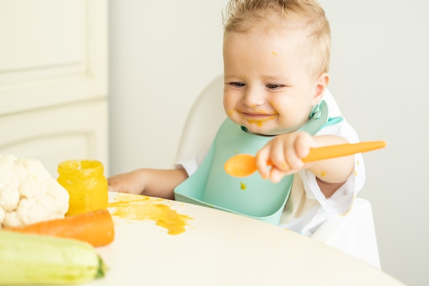 어린이 의자에 앉아 숟가락으로 야채 퓌레를 먹는 턱받이에 재미있는 아기 아이가 먹는 법을 배웁니다...