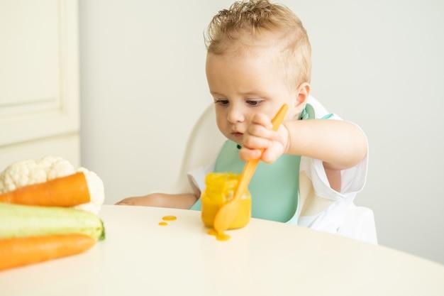 아이 의자에 앉아 숟가락으로 야채 퓌레를 먹는 턱받이에 재미있는 아기 먹는 법을 배웁니다