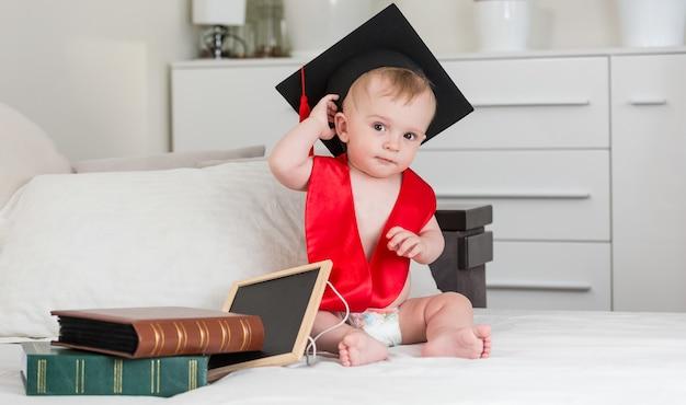 Забавный мальчик в черной выпускной кепке, держащей книгу