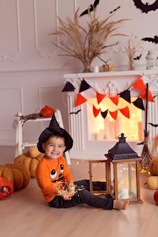 カボチャのジャックとほうきの屋内でハロウィーンの魔女の衣装で面白い男の子