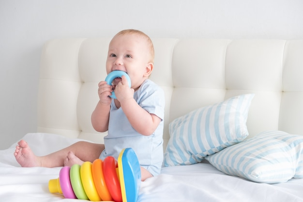 Funny baby boy sits on bed and play with a toy children's pyramid.