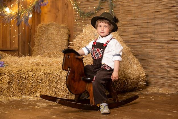 レトロな衣装を着ておもちゃの馬に座っている面白い男の子