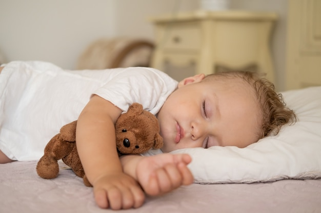 Funny baby boy sleeping on bed at home child hugging teddy bear
