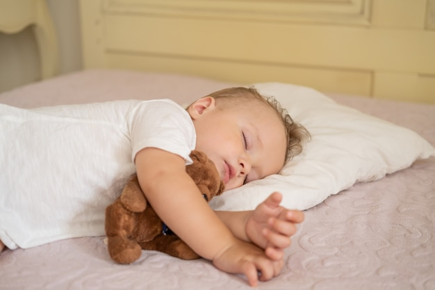 Funny baby boy sleeping on bed at home. child hugging teddy bear.