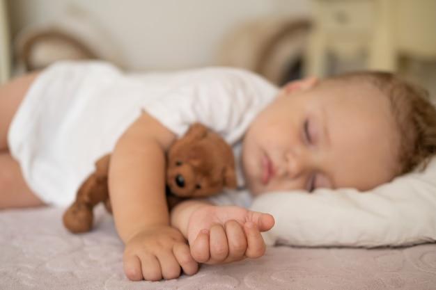집에서 침대에서 자고 있는 재미있는 아기 테디베어를 껴안고 손에 선택적 초점