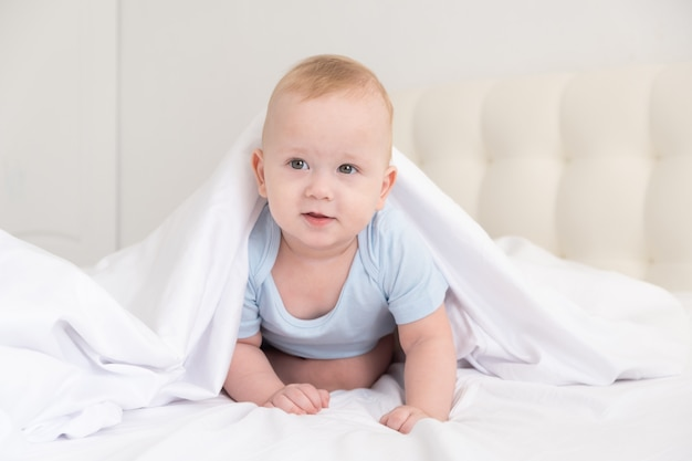 Funny baby boy smiling and lying on a white bedding at home.