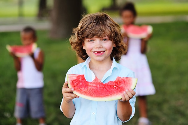 Забавный мальчик с вьющимися волосами ест спелый сочный арбуз и улыбается