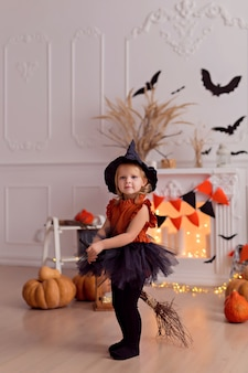 Funny baby girl in halloween witch costume with pumpkin jack and broom indoors