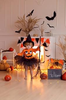 カボチャのジャックとほうきを屋内でハロウィーンの魔女の衣装で面白い赤ちゃん女の子
