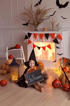 カボチャのジャックとほうきの屋内でハロウィーンの魔女の衣装で面白い女の赤ちゃん