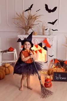 Смешная девочка в костюме ведьмы на хэллоуин с тыквенным гнездом и метлой в помещении